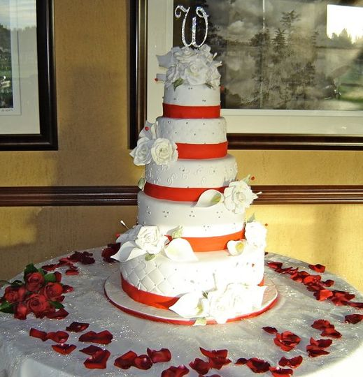 WHITE ROUND CAKE WITH RED RIBBON AND WHITE FLOWERS