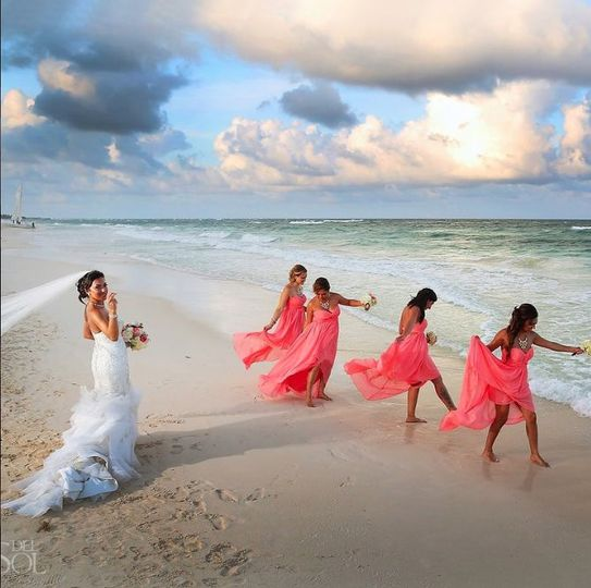 The bride and her bridesmaids by the shore
