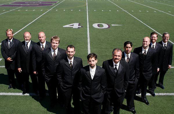 A 40 year sports nut groom with his groomsmen on the 40 yard line of a football field in Salinas