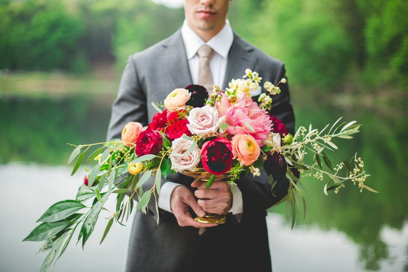 The groom holding her brides bouquet
