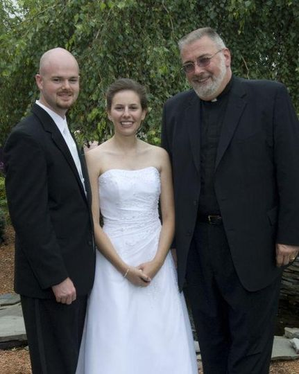 Happy newlyweds and officiant