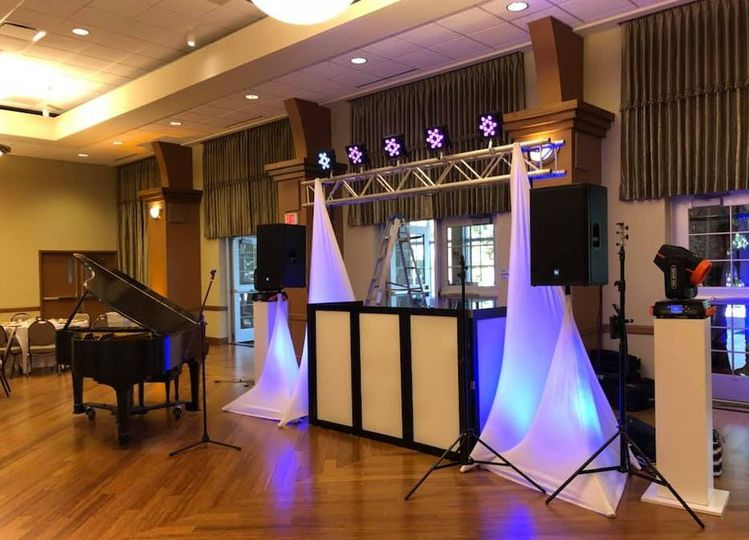DJ booth setup in front of a piano
