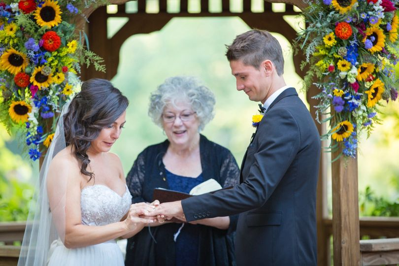 CT officiant Zita Christian guides the bride as she places the ring on her groom's finger | Photo by...
