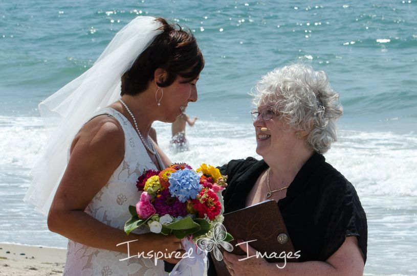 CT officiant Zita Christian shares a word with the bride on the beach in RI | Photo by Inspired...