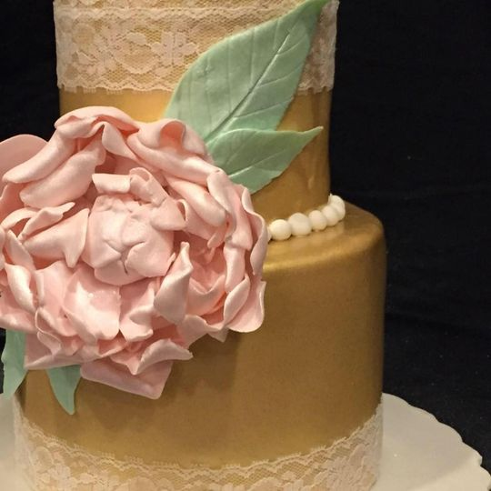 Golden brushed lace cake with handmade pink peony flower. Adorned with edible lace and pearls