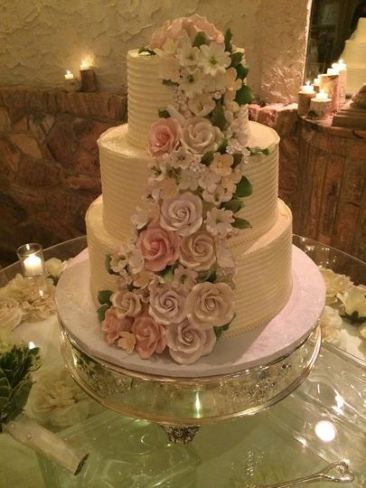 Buttercream three tier wedding cake adorned with handmade floral arrangement.