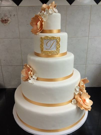 Five tier monogrammed wedding cake. Handmade magnolia and hydrangea arrangements.