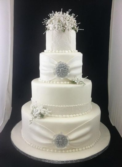 Four tier wedding cake with handmade brooches and stephanotis flowers. Gathered fabric and lace work...