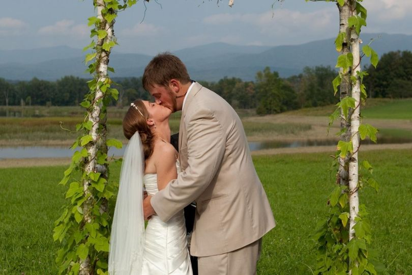 Newlyweds kiss by the field