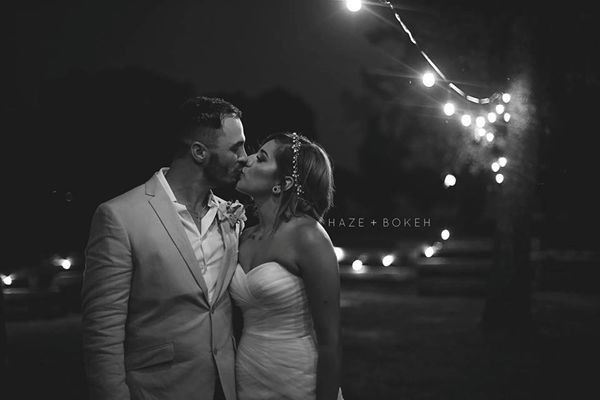 Newlyweds kissing under the lights