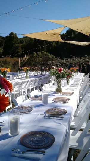 Tables were set in the field for a formal outdoor reception