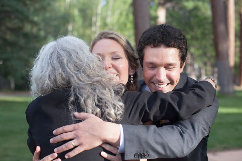 Newlyweds hugging the officiant