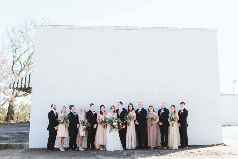 Newlyweds and their guests with a plain white backdrop