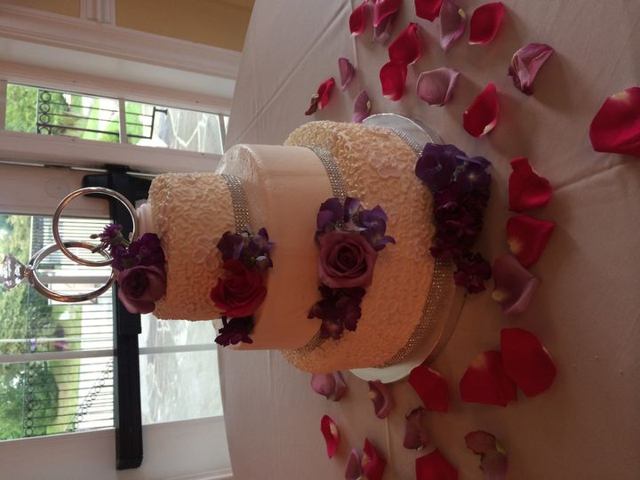3-tiered buttercream, fresh flowers, rhinestone base ribbons