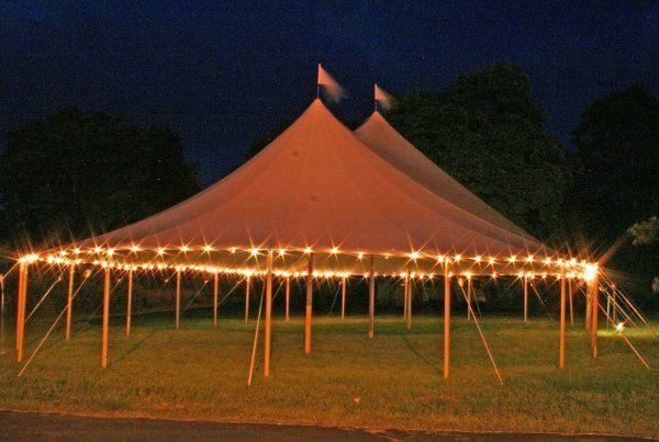 Under a Century pole tent with custom flooring, lighting and decor.