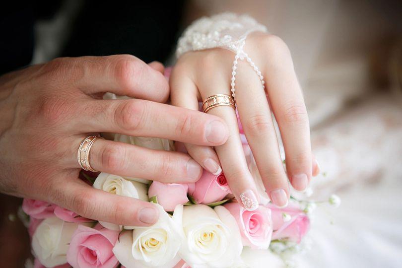 Bride & groom hands on bouquet
