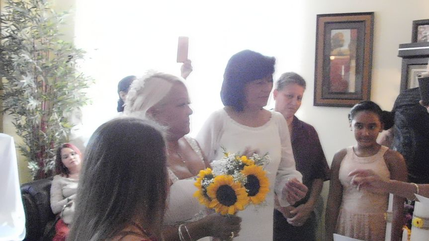 Gloria and Maribel in the center facing the wedding officiant.