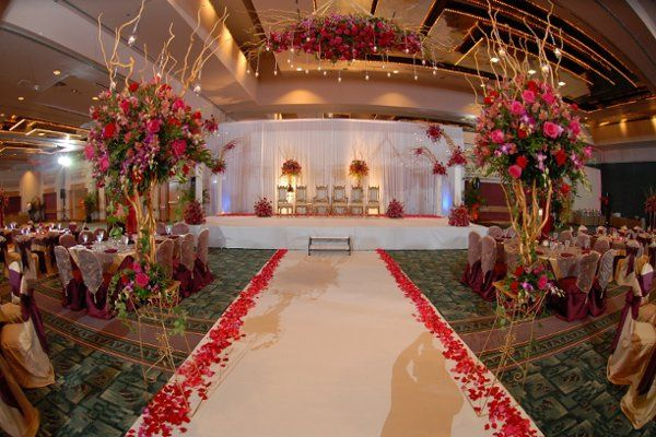 Breathtaking affair for 660 guest with thousands of red and fuchsia roses accented with Bombay...