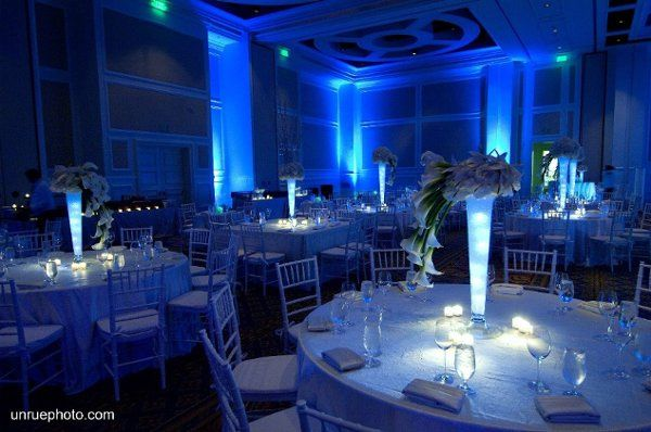 The room was illuminated blue with centerpiece illuminated a soft white.  Three different floral...