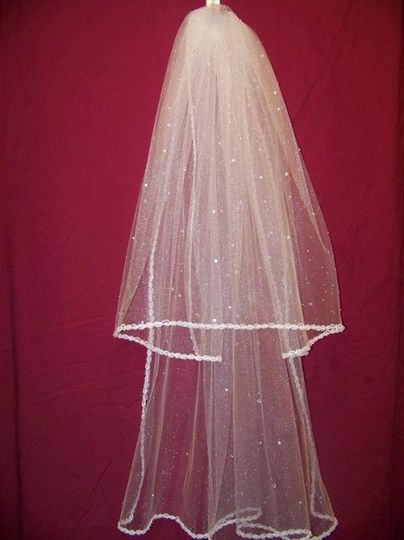 This is our traditional veil it is two tiers, square cut with white shimmer tulle. It is trimmed...