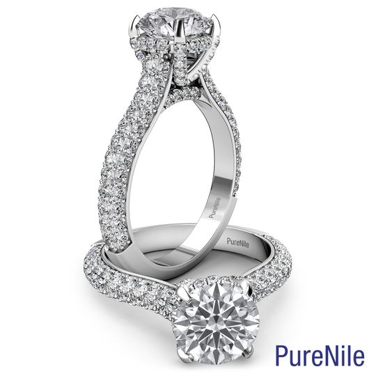 A gorgeous ring features a round cut diamond with three rows of round diamonds on shank and...
