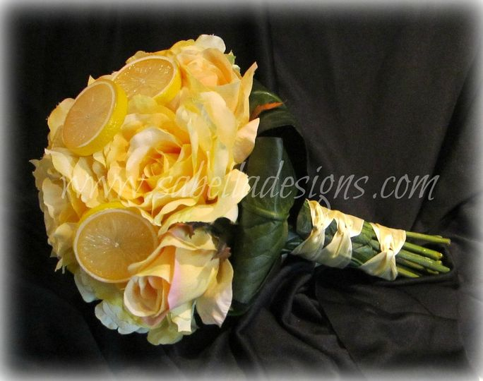 Stunning bouquet with creamy yellow roses, green leaves, and lemon accents make this a bouquet to...