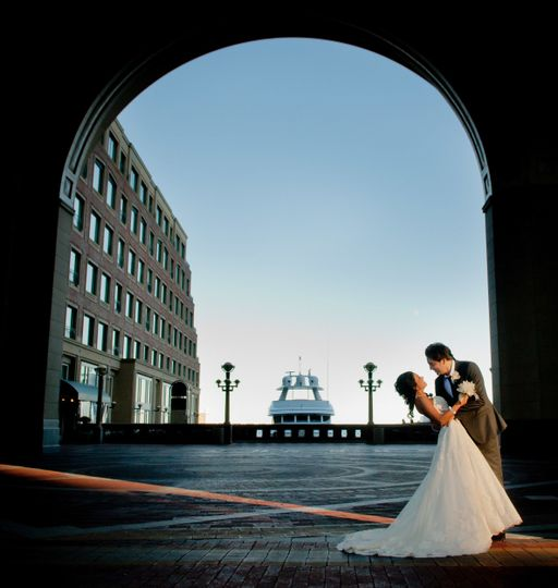 Boston wedding photography of Greek groom and Persian bride under multi-story arch at Boston Harbor...