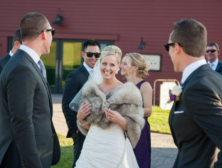 Bride in faux fur wrap surrounded by admiring groomsmen at the Barn at Gibbet Hill. ©2018 Fort Point...