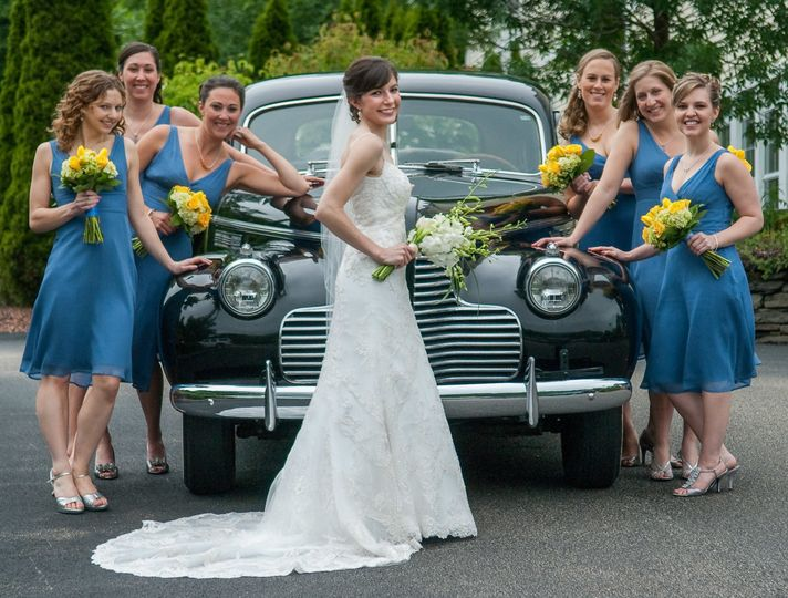 Bride and bridesmaids pose with antique Buick Super at Log Cabin Wedding in Holyoke. ©2018 Fort...
