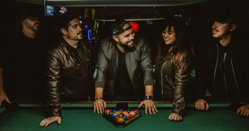 Band posing by a pool table