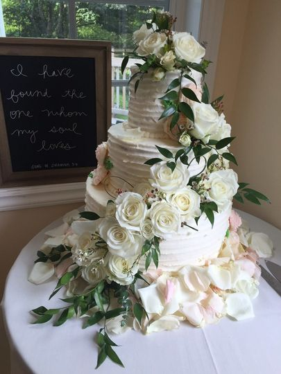 Cascading ivory and pale peach garden roses with trails of ruscus greenery complementing a three...