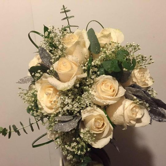 Ivory roses mixed with eucalyptus, ruscus, bear grass and a hint of baby's breath in a hand tied...
