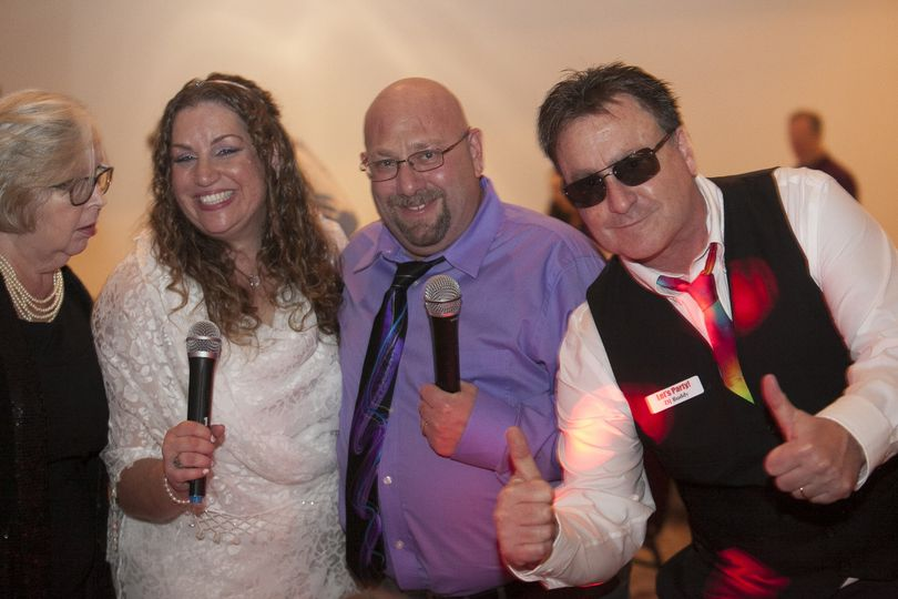 DJ Buddy of Let's Party! DJs teaching happy couple Marci & Elliot how to use the microphones.  We...