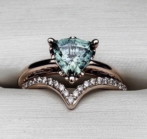 Custom Teal Sapphire Trillion cut engagement ring with chevron diamond band.