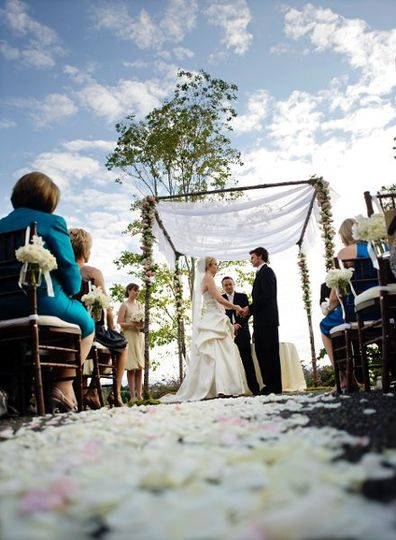 Ceremony decor of strung orchids, hurricanes with candles and rose petals.  Image by Joseph Milton