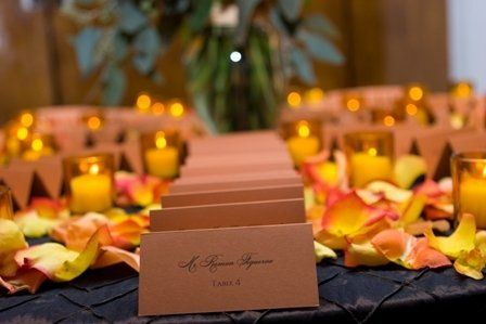 Spice escort cards, circus rose petals and amber votives.