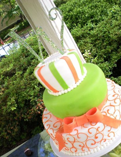 3 tiered fondant covered cake decorated with citrusy colors and topped with jeweled monogram topper.
