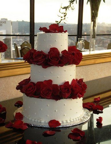 3 tiers buttercream covered cake separated by beautiful red roses