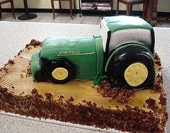 3D tractor cake resting on a field of carrot cake.