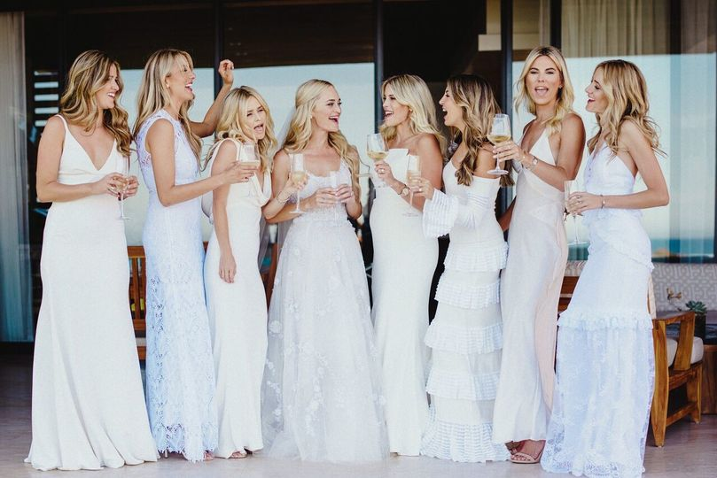Stunning bride and bridesmaids in a white-themed beach wedding