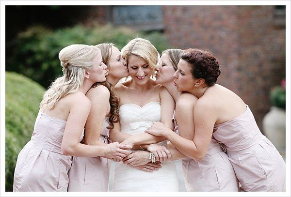 Bridesmaids kiss the bride