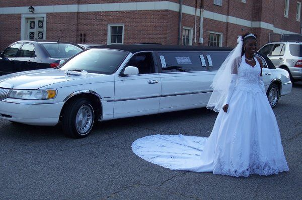 Bride in front of stretch limousine.