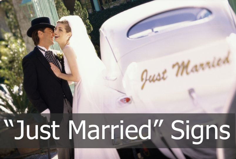 """Just Married"" signs on the side of the limousine."
