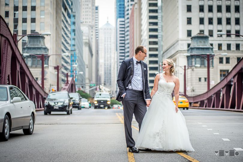 Bride and groom in the middle of a busy downtown Chicago street.
