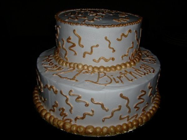 This is a two-tier cake iced in Vanilla Buttercream  with metallic -gold painted accents.