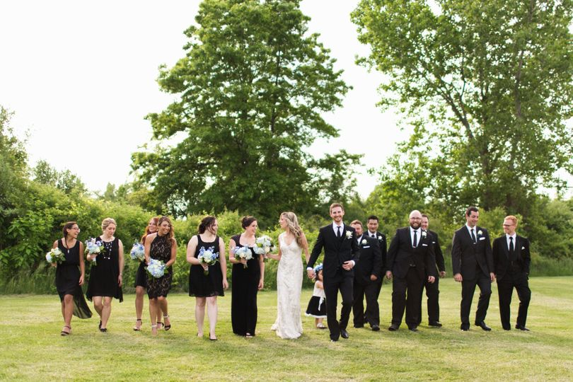 Couple walk along with bridesmaids and groomsmen
