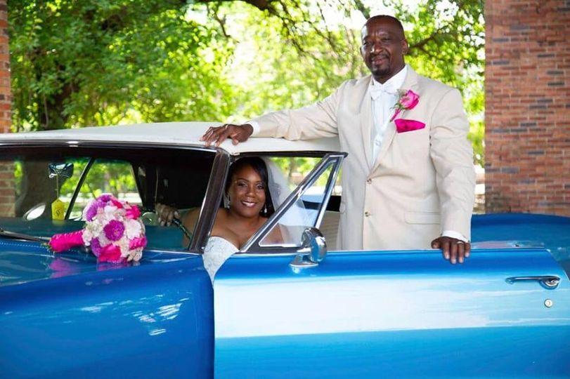 Newlyweds by their car