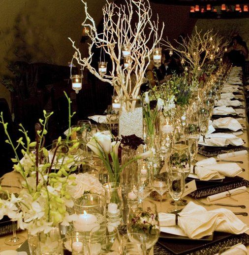 Table scape includes various vases each filled with a different flower.  Very dramatic look using...