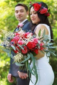 Unique bridal bouquet with red roses and leaves