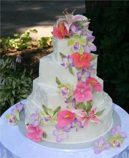 Hand-made sugar hibiscus, anthuriums, stargazer lilies and orchids on monogrammed buttercream...